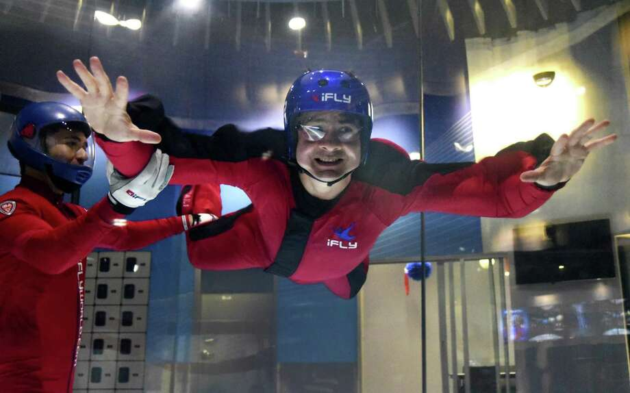 San Antonio Express-News reporter Rene Guzman skydives in the vertical wind tunnel with the help of instructor Ivan Castillon at iFly Indoor Skydiving center. Photo: Billy Calzada /San Antonio Express-News / San Antonio Express-News