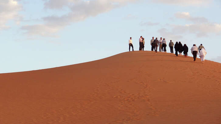 """Visitors and Aramco staff climb a dune at Shaybah, the base for Saudi Aramco's Natural Gas Liquids plant and oil production in the surrounding Shaybah field in Saudi Arabia's remote Empty quarter desert close to the United Arab Emirates, on May 10, 2016. Despite collapsed global oil prices, production is expanding at Shaybah, as it is in other units of the company at the centre of the kingdom's Vision 2030 drive for diversification away from oil. The Saudi government plans to sell less than five percent of the company in what officials say will be the world's largest-ever share offering, while transforming Saudi Aramco into """"a global industrial conglomerate"""". By 2020 the company says it will have tripled its gas processing capacity from levels at the turn of the century. / AFP PHOTO / IAN TIMBERLAKEIAN TIMBERLAKE/AFP/Getty Images"""