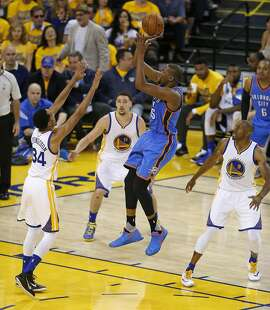 Oklahoma City Thunder's Kevin Durant scores between Golden State Warriors' Shaun Livingston, Klay Thompson and Andre Iguodala in 4th quarter during Game 1 of NBA Playoffs' Western Conference Finals at Oracle Arena in Oakland, Calif., on Monday, May 16, 2016.