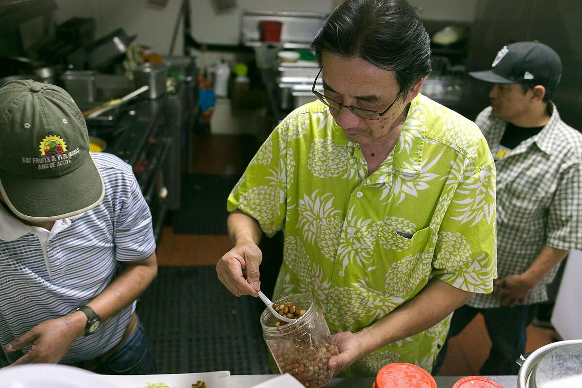 Owner, William Lue helps prepare a salad in the kitchen at Tender Loving Food in S.F.