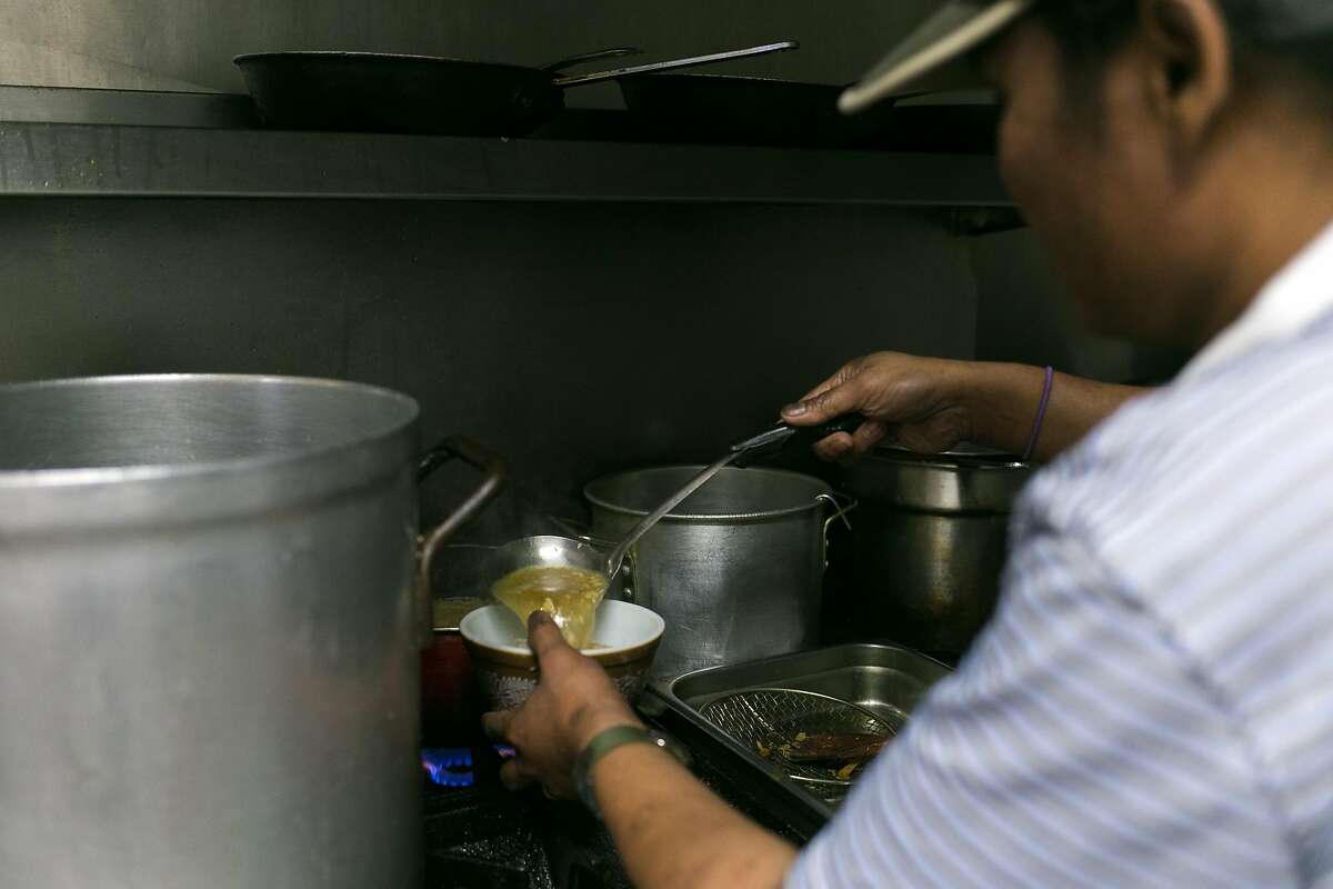 San Oo pours hot broth into a bowl at Tender Loving Food in S.F.
