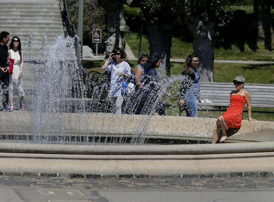 A woman cooled her toes in a fountain in front of the California Academy of Sciences on May 13, 2014 in San Francisco, Calif. On Tuesday, hot weather is forecast for the Bay Area with temperatures hitting the low to mid 90s in parts of the East Bay. Photo: Brant Ward, The Chronicle