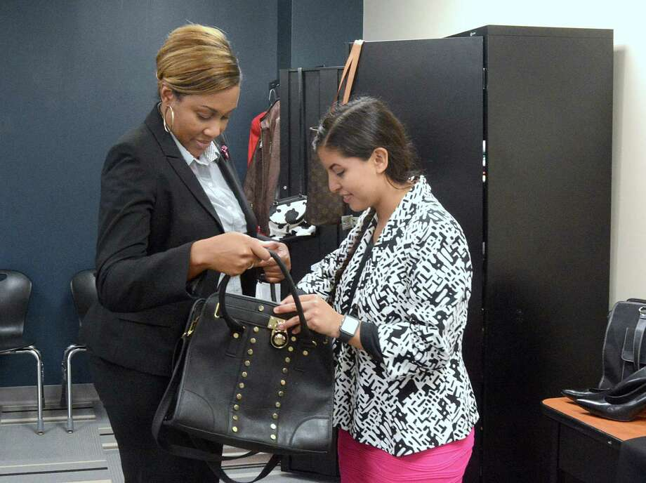 "TeKedra Pierre, Wunsche High School medical academy coordinator, helps junior Daniela Trujillo choose a jacket and purse at the school's ""Wunsche Closet,"" which provides students with business attire, including suits, ties, dresses, skirts, belts and shoes that they can wear for job and internship interviews. Photo: Z-David Hopper"