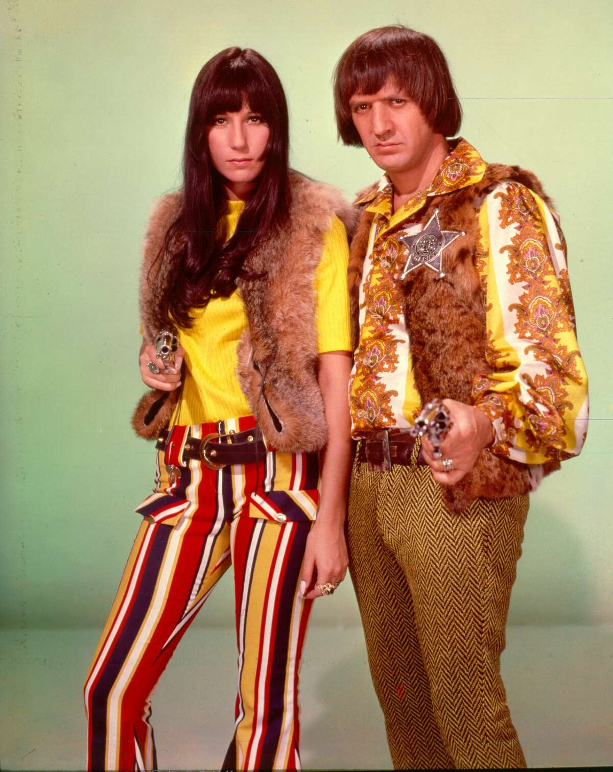 Entertainers Sonny Bono & Cher point guns toward the camera as they pose for a portrait, circa 1968.