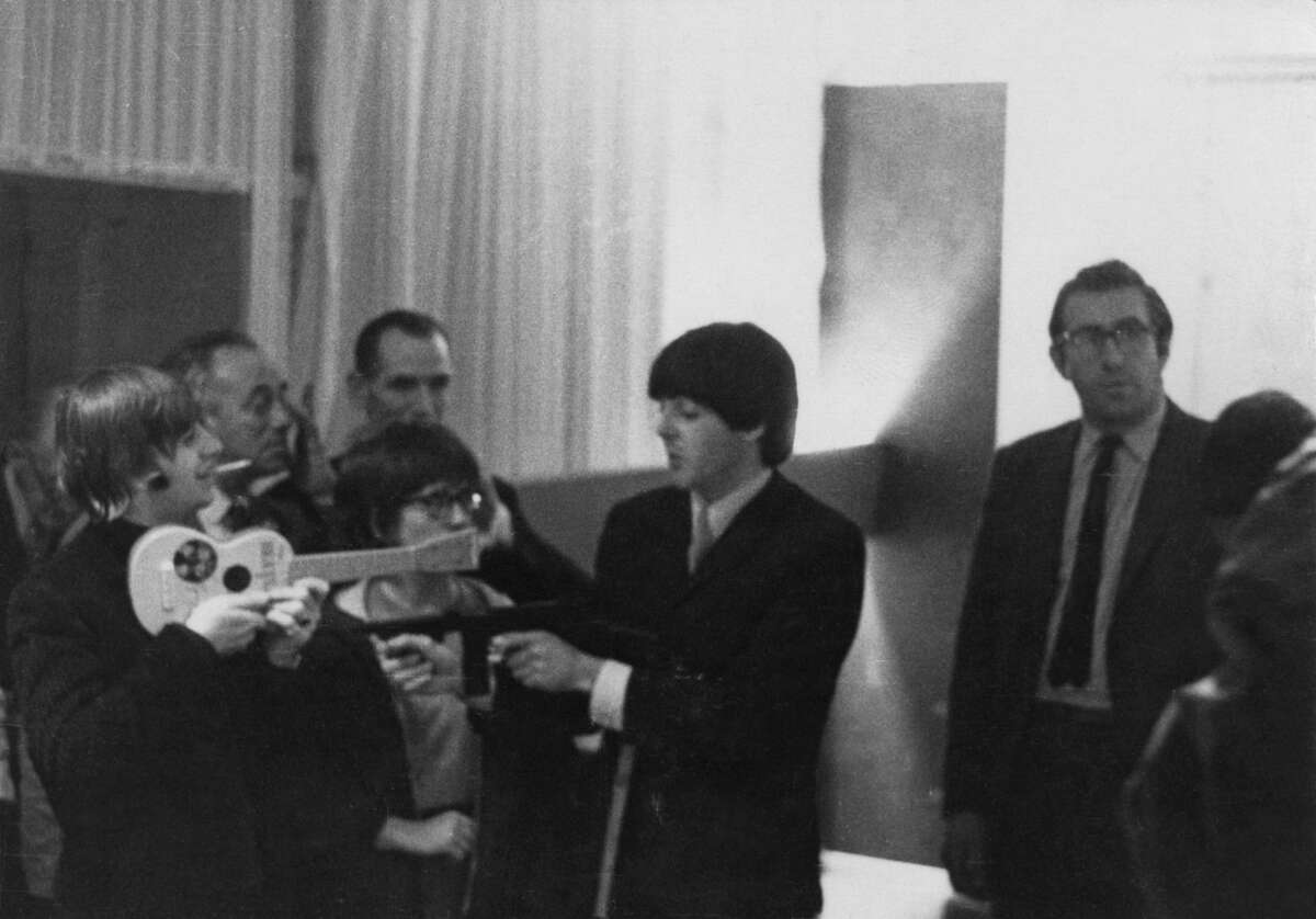 Paul McCartney points a replica machine gun at Ringo Starr while Ringo points a toy Beatle guitar at Paul backstage at the Gaumont Cinema in Southampton, England on Nov. 6, 1964.