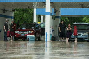 People take shelter in a car wash near the Timber Lakes Timber Ridge subdivision on Monday, April 18, 2016, in The Woodlands.