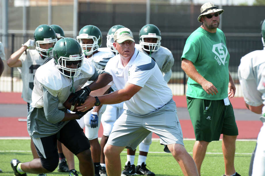 Spring head football coach Sam Parker, center, hands off to running back A'Zavier Roane during an offensive drill at spring practice earlier this month. Photo: Jerry Baker, Freelance