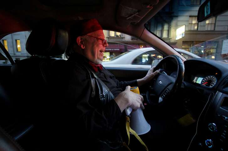 """Buzz Brooks scans the sidewalks while holding the bullhorn he uses to lure customers to his cab when Uber rides are surging on a Saturday night on May 13, 2016 in San Francisco, Calif. Brooks, who has been a cab driver in the city for over 35 years, started singing his own cabaret tunes to customers ten years ago, calling it the Kabaret Kab Experience. """"Not many cab drivers these days look forward to going to work,"""" says Brooks, but because of the cabaret, """"I actually look forward to doing it."""""""