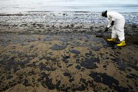 FILE - In this May 21, 2015, file photo, a worker removes oil from sand at Refugio State Beach, north of Goleta, Calif. An underground pipe, owned by Plains All American Pipeline, spewed oil down a culvert and into the Pacific on May 19 before it was shut off. Exxon Mobil Corp. won approval Monday, Feb. 1, 2016, for its plan to use trucks to move more than 17 million gallons of oil stranded in storage tanks after a California pipeline break in May, despite concerns from an environmental group that highway safety could be jeopardized. (AP Photo/Jae C. Hong, File)