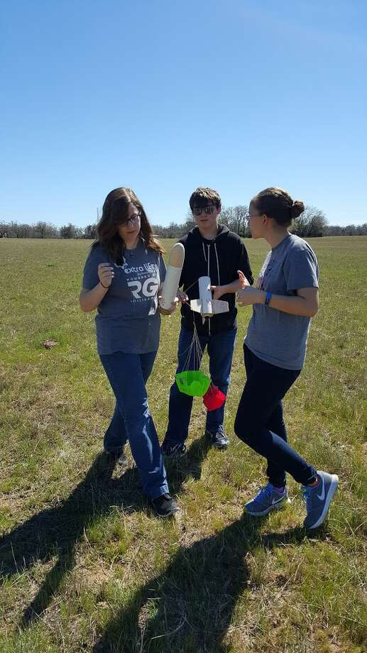 Roosevelt rocketry club team members Caylee Davis (left), Ethan Bracy and Ana Wilson talk about a launch after retrieving their fired rocket. Photo: Courtesy Photo