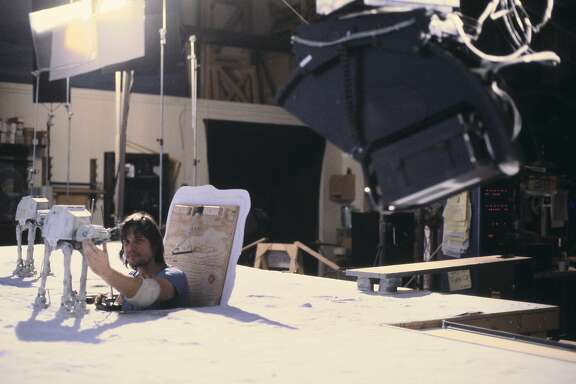"Jon Berg pops out of a hatch to work on one of the snow walker puppets for the ice planet Hoth battle scene in the 1980 movie ""The Empire Strikes Back."""