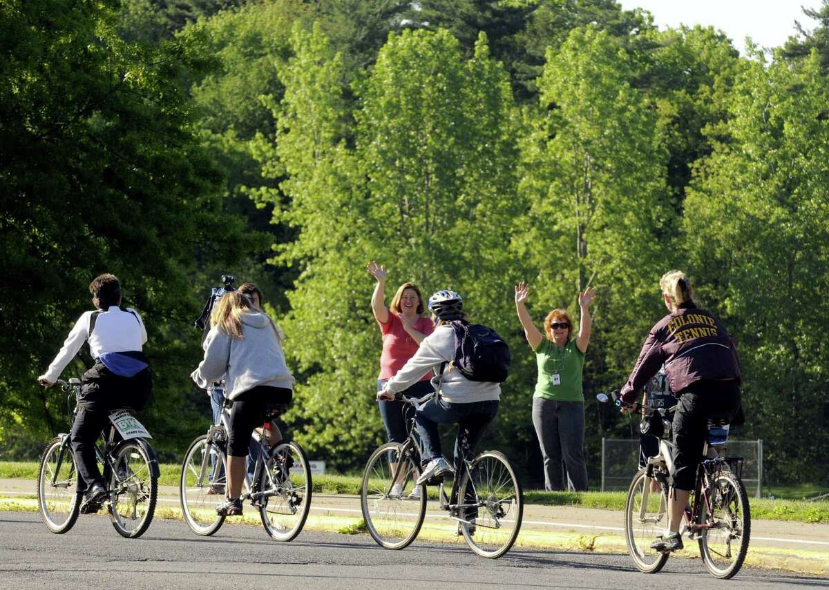 Teachers and staff from Lisha Kill Middle School who took part in National Bike to Work Day are cheered on as they arrive at the school in Colonie N.Y. Friday May 18, 2012. (Michael P. Farrell/Times Union)