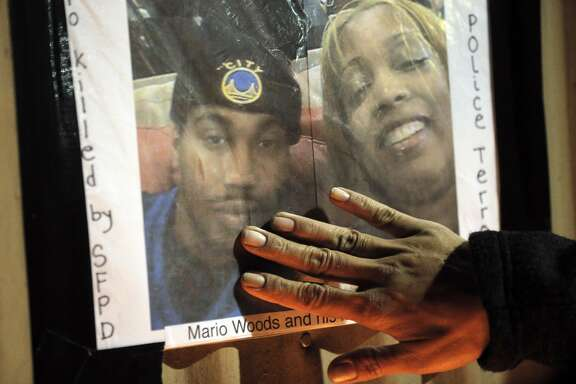 A hand reaches out to touch a photo of Mario Woods and his mom, Gwen Woods, at the site where Mario Woods was shot and killed by San Francisco Police to commemorate the young man in the Bayview district of San Francisco, Calif., on Thursday, December 3, 2015.
