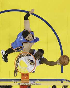 Golden State Warriors' Draymond Green, bottom, drives past Oklahoma City Thunder's Enes Kanter during the second half in Game 1 of the NBA basketball Western Conference finals Monday, May 16, 2016, in Oakland, Calif. Oklahoma City won 108-102. (AP Photo/Marcio Jose Sanchez)
