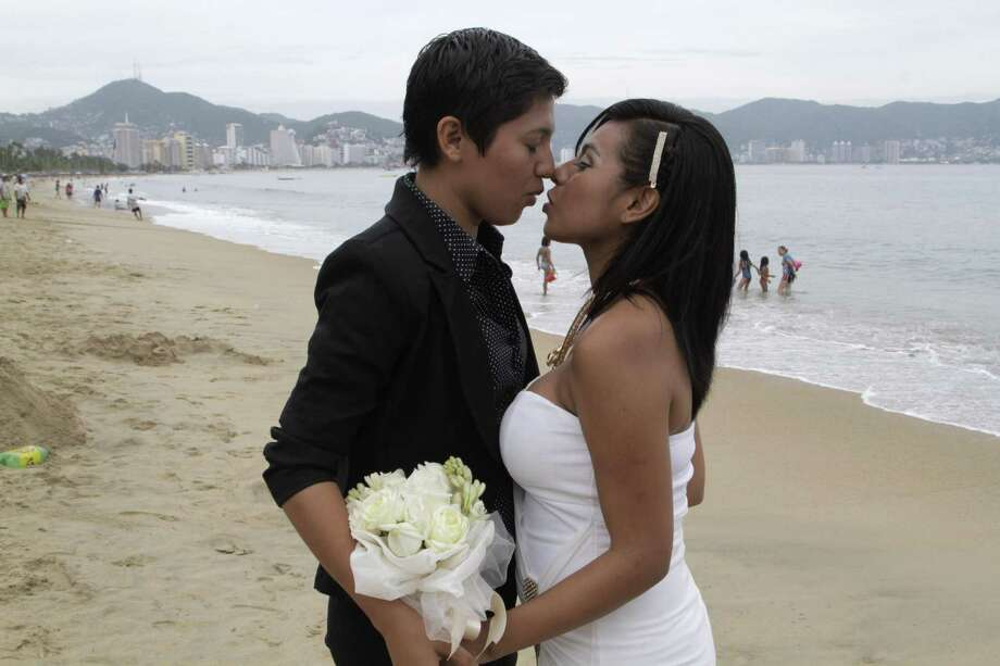 FILE - In this July 10, 2015 file photo, an unidentified same-sex couple kisses during a group wedding for lesbian, gay, bisexual and transgender couples in Acapulco, Mexico. Mexican President Enrique Pena Nieto has proposed legalizing gay marriage. Pena Nieto said Tuesday, May 17, 2016 that he signed initiatives that would seek to enshrine same-sex marriage in the country';s constitution and the federal civil code.  (AP Photo/Bernandino Hernandez, File) Photo: Bernandino Hernandez, STR / AP