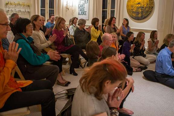 A group of friends gather in the home of Norman and Norah Stone to listen to the guided meditation session by Orgyen Chowang Rinpoche  on Tuesday, Sept. 15, 2015 in San Francisco, Calif.  Meditation is fast becoming a mainstream health practice and classes are being offered in more places than just the local community center.