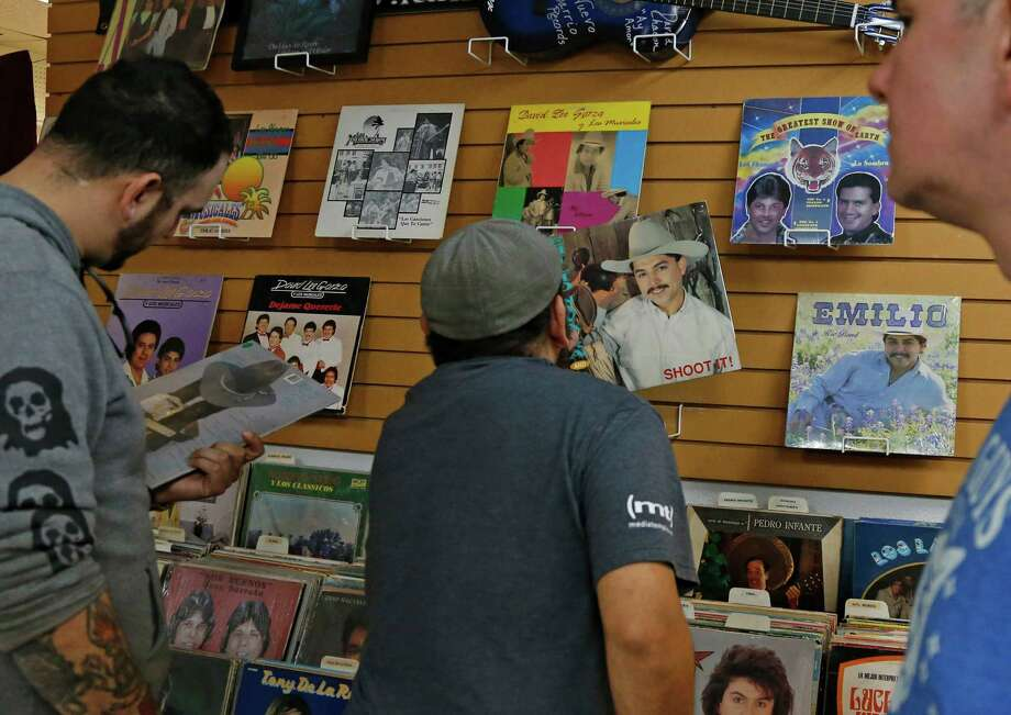 George Mendoza checks out one of Emilio Navaira album covers at Janie's Record Shop on Tuesday. Photo: Ron Cortes /For The Express-News