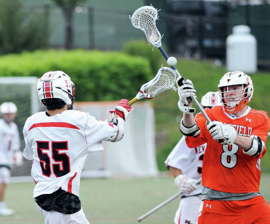 New Canaan's Nciholas Cravatto (#55), left, passes while being defended by Chris Costello (#8) of Ridgefield during the boys high school lacrosse match between New Canaan High School and Ridgefield High School at New Canaan. Conn., Tuesday, May 17, 2016. Photo: Bob Luckey Jr. / Hearst Connecticut Media / Greenwich Time