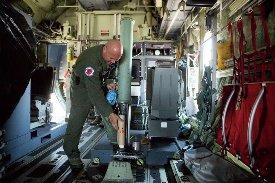 Master Sgt. Ed Scherzer shows how a spring-loaded cannon with small tubes and packed with instruments, known as dropsonde, is dropped into a hurricane. Photo: Marie D. De Jesus, Staff / © 2016 Houston Chronicle