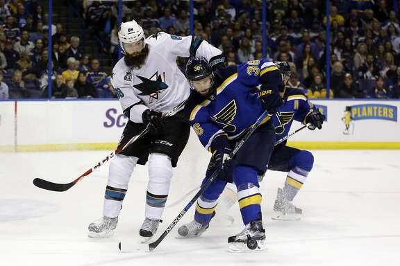 St. Louis Blues right wing Troy Brouwer (36) tries to control the puck against San Jose Sharks defenseman Brent Burns (88) during the first period in Game 2 of the NHL hockey Stanley Cup Western Conference finals, Tuesday, May 17, 2016, in St. Louis. (AP Photo/Jeff Roberson)