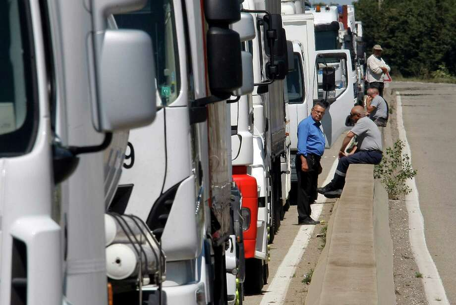 Truck drivers block the road near Fos-sur-Mer, France, on Tuesday. Similar actions are occurring across France to protest a bill that would cut overtime pay. Photo: Claude Paris, STR / AP