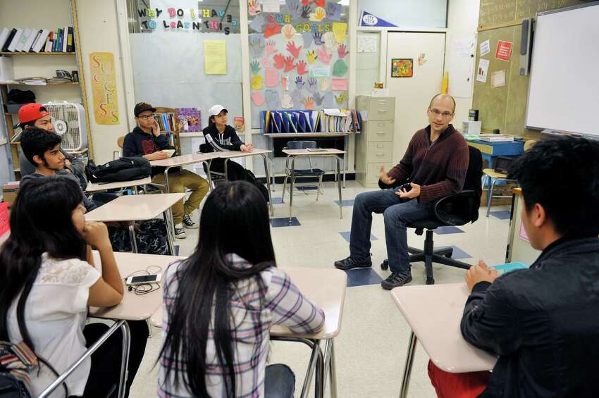 Albany High School English teacher, Brian Huskie, right, talks with high school refugee students, from background to foreground, Beya Paw, Blah Hsae, Soe Aung, Saad Bene Jamiel, Uma Siwakoti, Say Htoo, and Shar Reh on Tuesday, May 17, 2016, in Albany, N.Y. (Paul Buckowski / Times Union)