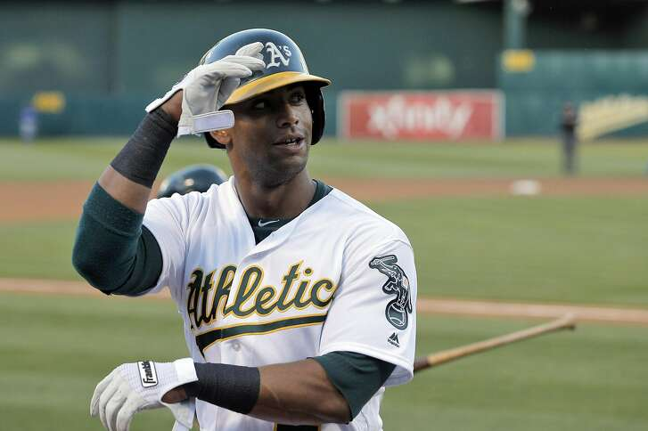Khris Davis (2) salutes teammates after hitting a solo homerun in the second inning as the Oakland Athletics played the Texas Rangers at the Oakland Coliseum in Oakland, Calif., on Tuesday, May 17, 2016.
