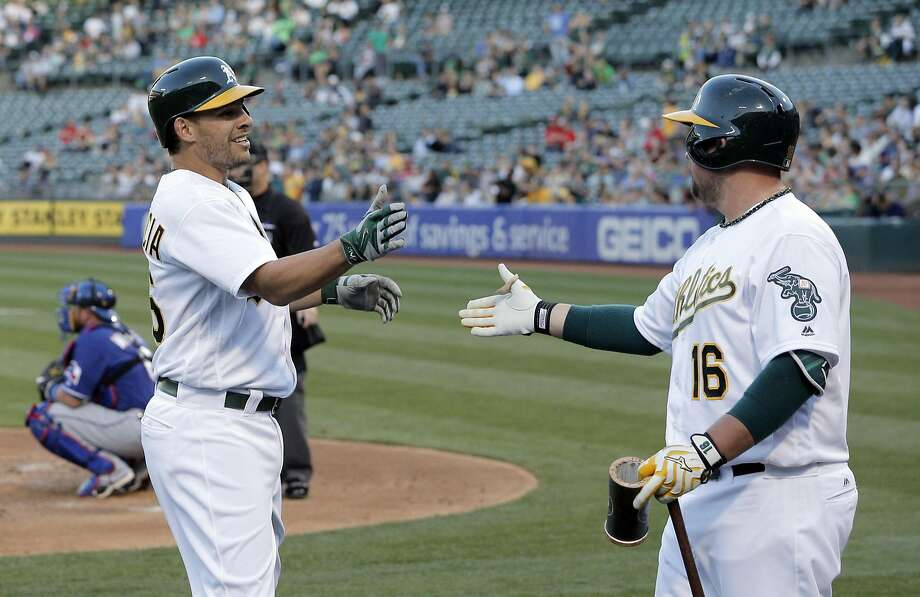 Danny Valencia (26) high fives Billy Butler (16) after hitting a solo homerun in the second inning as the Oakland Athletics played the Texas Rangers at the Oakland Coliseum in Oakland, Calif., on Tuesday, May 17, 2016. Photo: Carlos Avila Gonzalez, The Chronicle