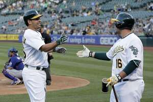 Danny Valencia (26) high fives Billy Butler (16) after hitting a solo homerun in the second inning as the Oakland Athletics played the Texas Rangers at the Oakland Coliseum in Oakland, Calif., on Tuesday, May 17, 2016.