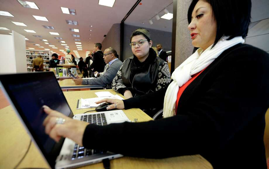 Affordable Care Act health insurance marketplace navigator Leticia Chaw, right, helps gather information for Jennifer Sanchez  re-enroll in a health insurance plan Friday, Nov. 14, 2014, in Houston.  (AP Photo/David J. Phillip Photo: David J. Phillip, STF / AP
