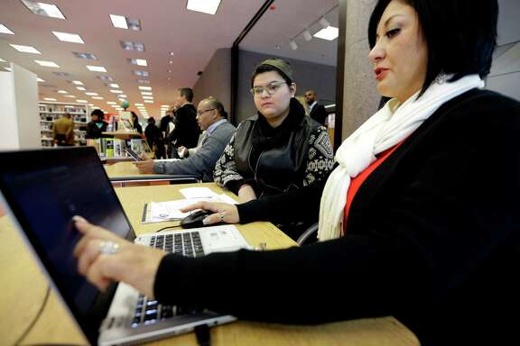 Affordable Care Act health insurance marketplace navigator Leticia Chaw, right, helps gather information for Jennifer Sanchez  re-enroll in a health insurance plan Friday, Nov. 14, 2014, in Houston. Community groups and health advocates are reaching out to some of the state's largest pockets of uninsured ahead of the second round of open enrollment under the Affordable Care Act. (AP Photo/David J. Phillip