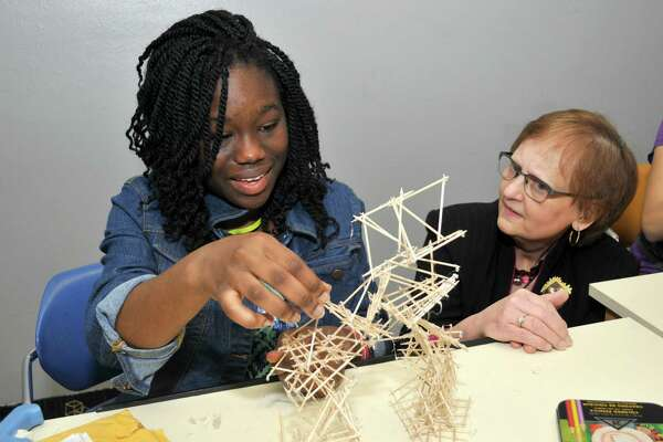 Eileen Montgomery, chair of the visual arts department at the High School for Performing and Visual Arts, eyes a project of ninth-grade student Renee Peters. Montgomery is retiring this month from HSPVA, where she has been since 1989.
