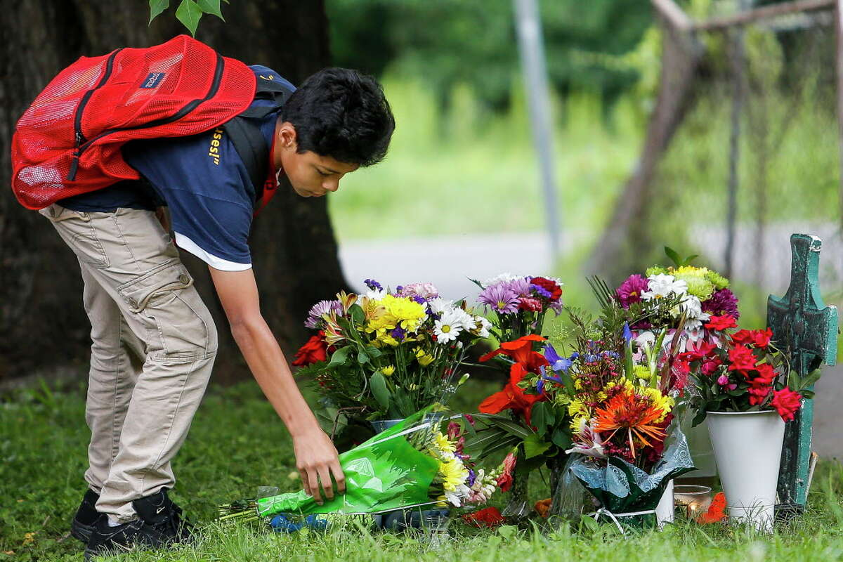 Christopher Martinez, 14, places flowers at a memorial for his classmate, 11-year-old Josue Flores, on his way to school Wednesday, May 18, 2016. Flores was stabbed to death while walking home from Marshal Middle School Tuesday afternoon. The two were supposed to go skateboarding together this weekend.