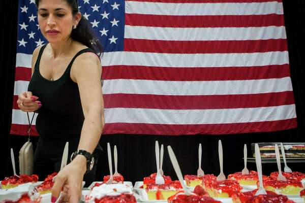 """Kendra Maayah of Pasadena takes a slice of the """"World's Largest Strawberry Shortcake"""" during last year's Pasadena Strawberry Festival."""