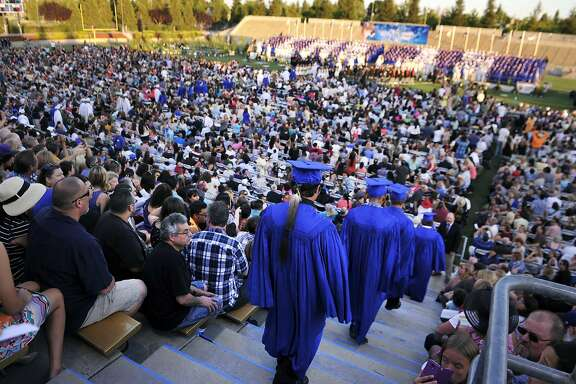 Graduating seniors including Christian Titman, wearing a feather at the end of the line, enter Lamonica Stadium for Clovis High's graduation ceremony Thursday, June 4, 2015, in Clovis, Calif. The Native American student is wearing an eagle feather to his high school graduation after resolving a court fight with a California school district over the sacred object. (Eric Paul Zamora/The Fresno Bee via AP)
