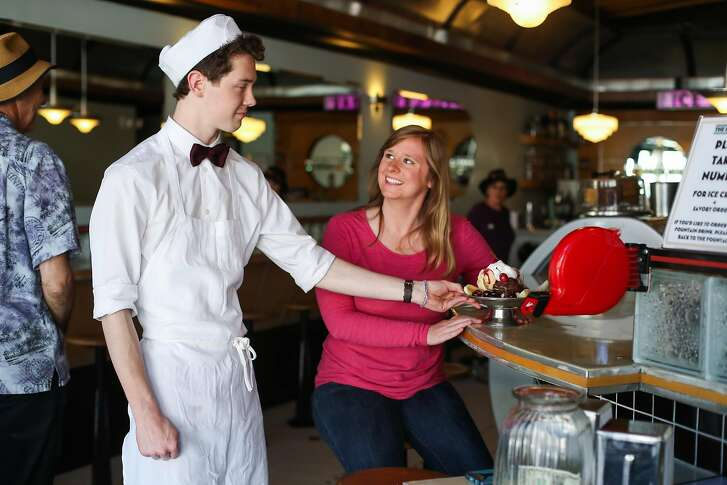 Elliot Young (left), of the Ice Cream Bar in Cole Valley, serves Brianna Rader, CEO of the app Juicebox, an ice cream sundae in San Francisco, California, on Tuesday, May 17, 2016.
