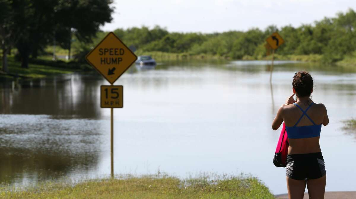 Regina Salinas takes pictures of flooding on Oso Parkway on Monday, May 16, in Corpus Christi. Thunderstorms in South Texas that dumped up to a foot of rain have led to flood-related rescues in Corpus Christi and sewage spilled into a creek.
