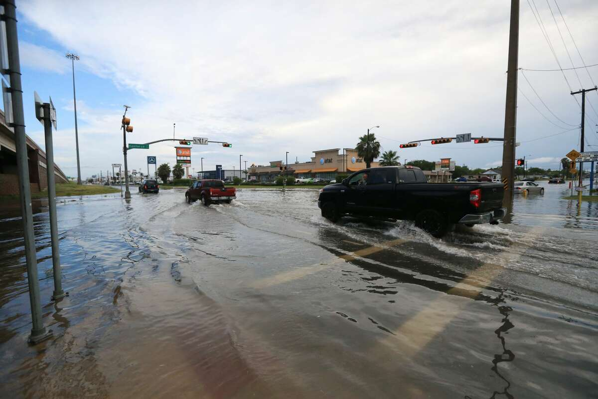 Vehicles pass through the intersection of South Padre Island Drive and Kostoryz Road on Monday, May 16 in Corpus Christi. Thunderstorms in South Texas that dumped up to a foot of rain have led to flood-related rescues in Corpus Christi and sewage spilled into a creek.
