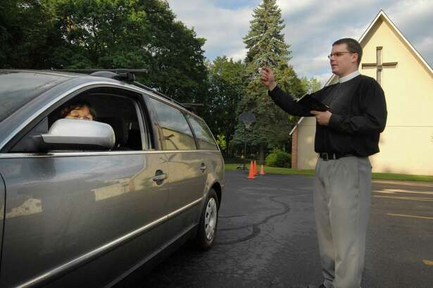 """Rev. Adam Egan blesses Gail Richardson's 2003 VW Passat during a """"First Day of School Blessing"""" event  at St. Stephen's Episcopal Church in Elsmere, Wednesday morning September 8, 2010. Rev. Egan, church staff and clergy members, offered coffee, juice, and a blessing of your means of transportation  from 6:30am till 9am at the corner of Elsmere Avenue and Poplar Drive. (Will Waldron / Times Union)"""