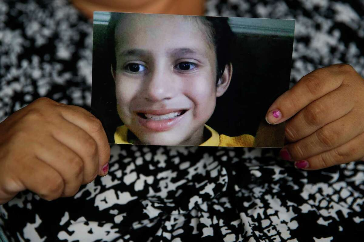 Maria Flores holds up a picture of her son, 11-year-old Josue Flores, who was stabbed to death while walking home from Marshal Middle School a few blocks from their home Tuesday afternoon.