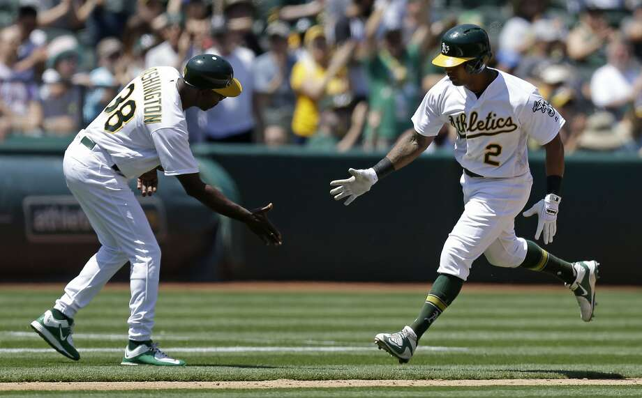 Oakland Athletics' Khris Davis, right, is congratulated by third base coach Ron Washington after hitting a home run off Texas Rangers' Martin Perez in the sixth inning of a baseball game, Wednesday, May 18, 2016, in Oakland, Calif.  Photo: Ben Margot, Associated Press