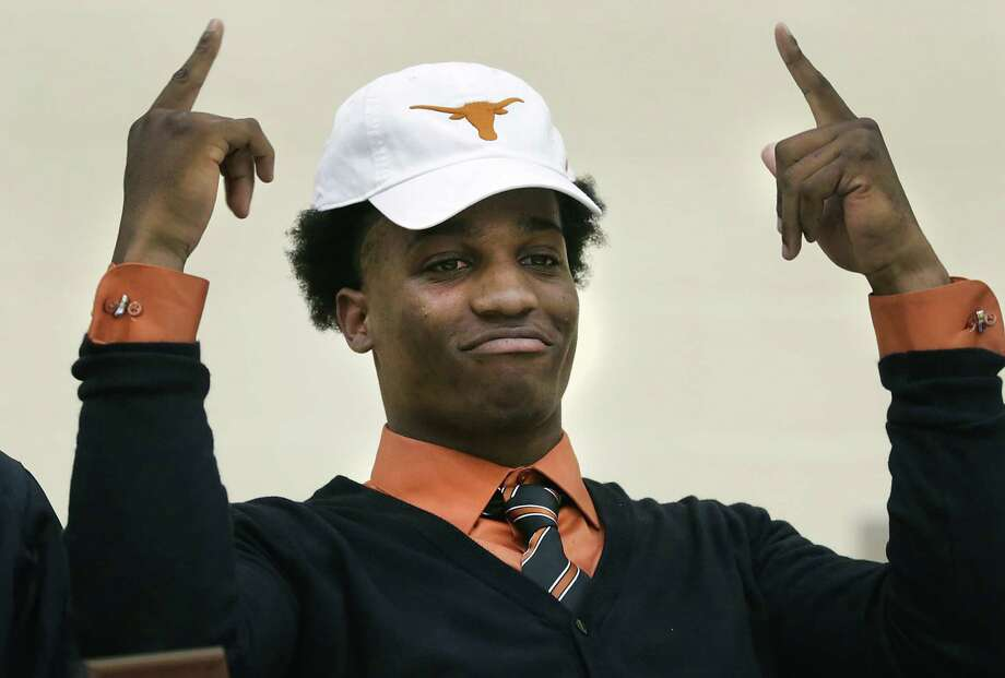 Derick Roberson, of Brennan High School, puts on a UT hat as he signs with the University of Texas football team.  Wednesday, Feb. 5, 2014. Photo: BOB OWEN, Staff / San Antonio Express-News / © 2012 San Antonio Express-News
