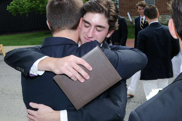 Eric Ganshaw, left, holds his Brunswick School dipolma as he hugs a fellow graduate after the commencement at the school in Greenwich, Conn., Wednesday, May 18, 2016. Educator, author, activist and former National Football League player Joe Ehrmann was the commencement speaker.