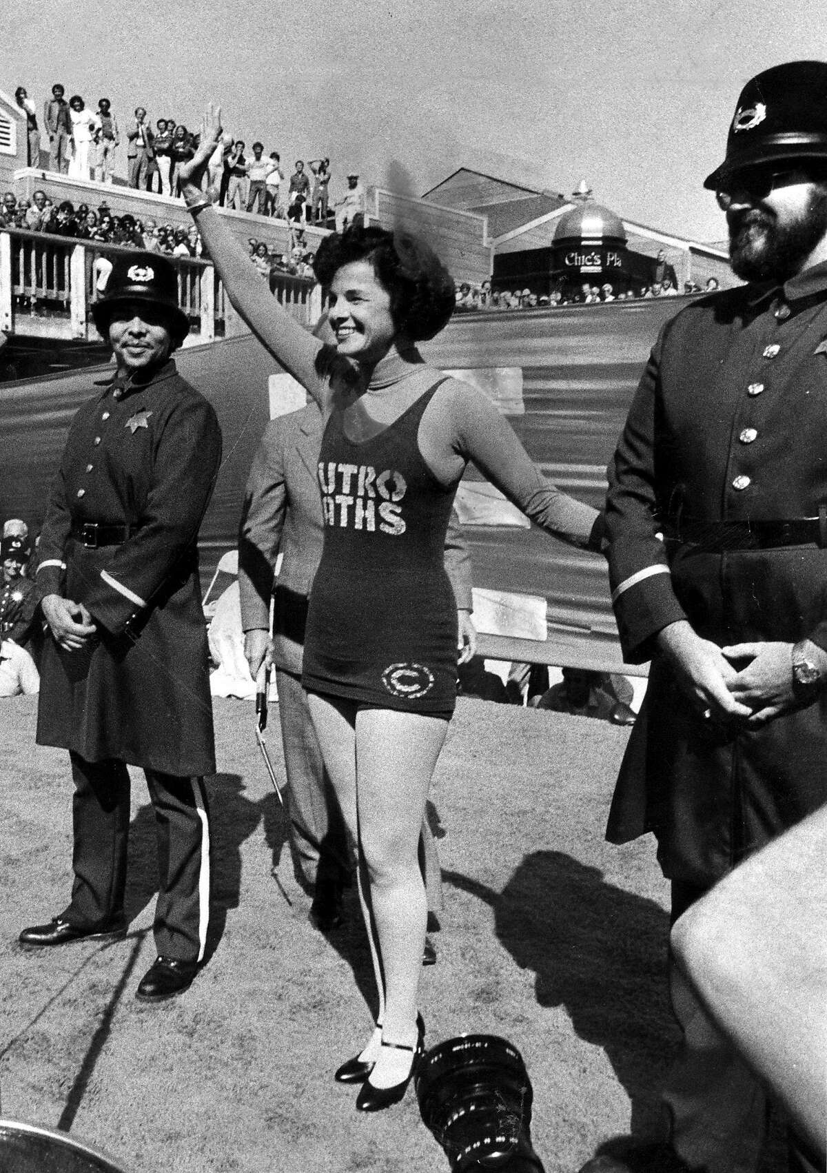 Supervisor Dianne Feinstein wearing a Sutro Baths tank suit, prepares to cut the ribbon at the opening of Pier 39 development.
