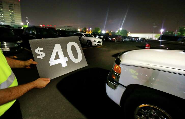 A parking attendant removes a sign for $40 parking near Minute Maid Park in Houston. ( Mark Mulligan / Houston Chronicle )