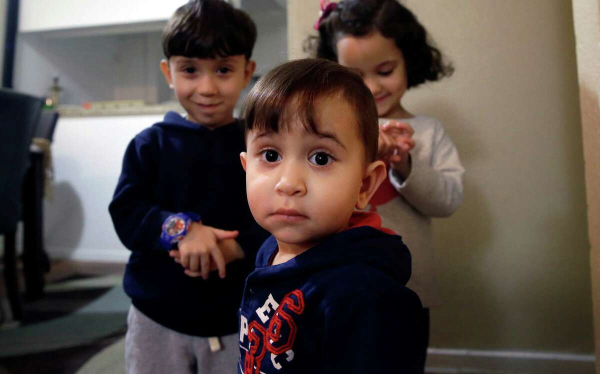 Syrian refugee Mohammad word al Jaddou, front, stands in front of his siblings twins Maria, right, and Hasan at their apartment in Dallas. The 30-year-old al Bashar al Jaddou decided to leave Syria in 2012 after his familyÂ?'s home in Homs was bombed and there was nowhere safe left to live. (LM Otero / Associated Press)