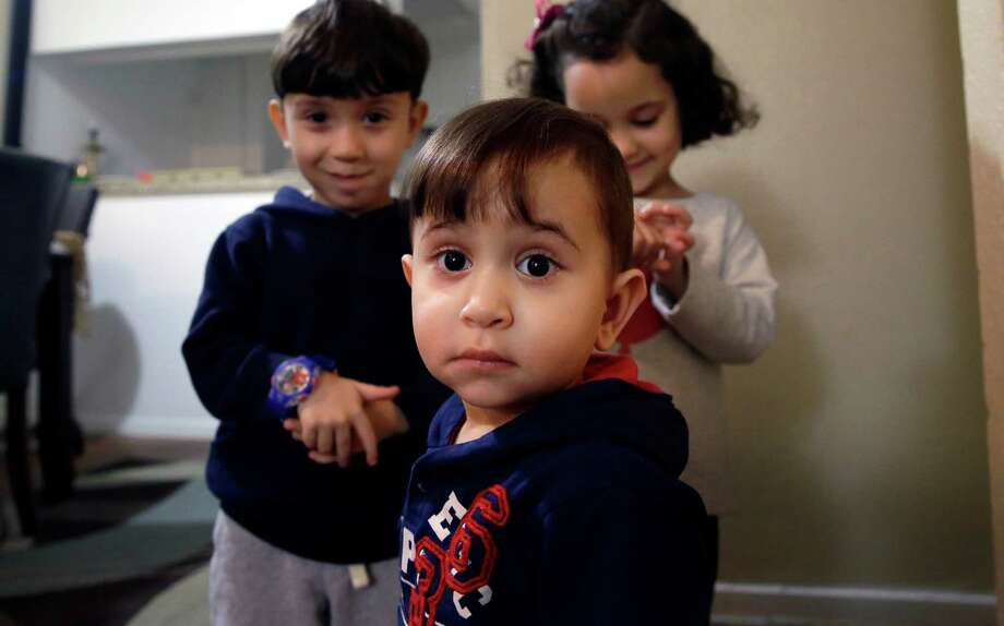 Syrian refugee Mohammad word al Jaddou, front, stands in front of his siblings twins Maria, right, and Hasan at their apartment in Dallas. The 30-year-old al Bashar al Jaddou decided to leave Syria in 2012 after his family's home in Homs was bombed and there was nowhere safe left to live. (LM Otero / Associated Press) Photo: LM Otero, STF / AP
