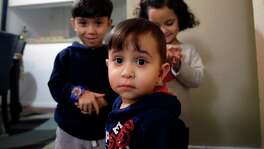 Syrian refugee Mohammad word al Jaddou, front, stands in front of his siblings twins Maria, right, and Hasan at their apartment in Dallas. The 30-year-old al Bashar al Jaddou decided to leave Syria in 2012 after his family's home in Homs was bombed and there was nowhere safe left to live. (LM Otero / Associated Press)
