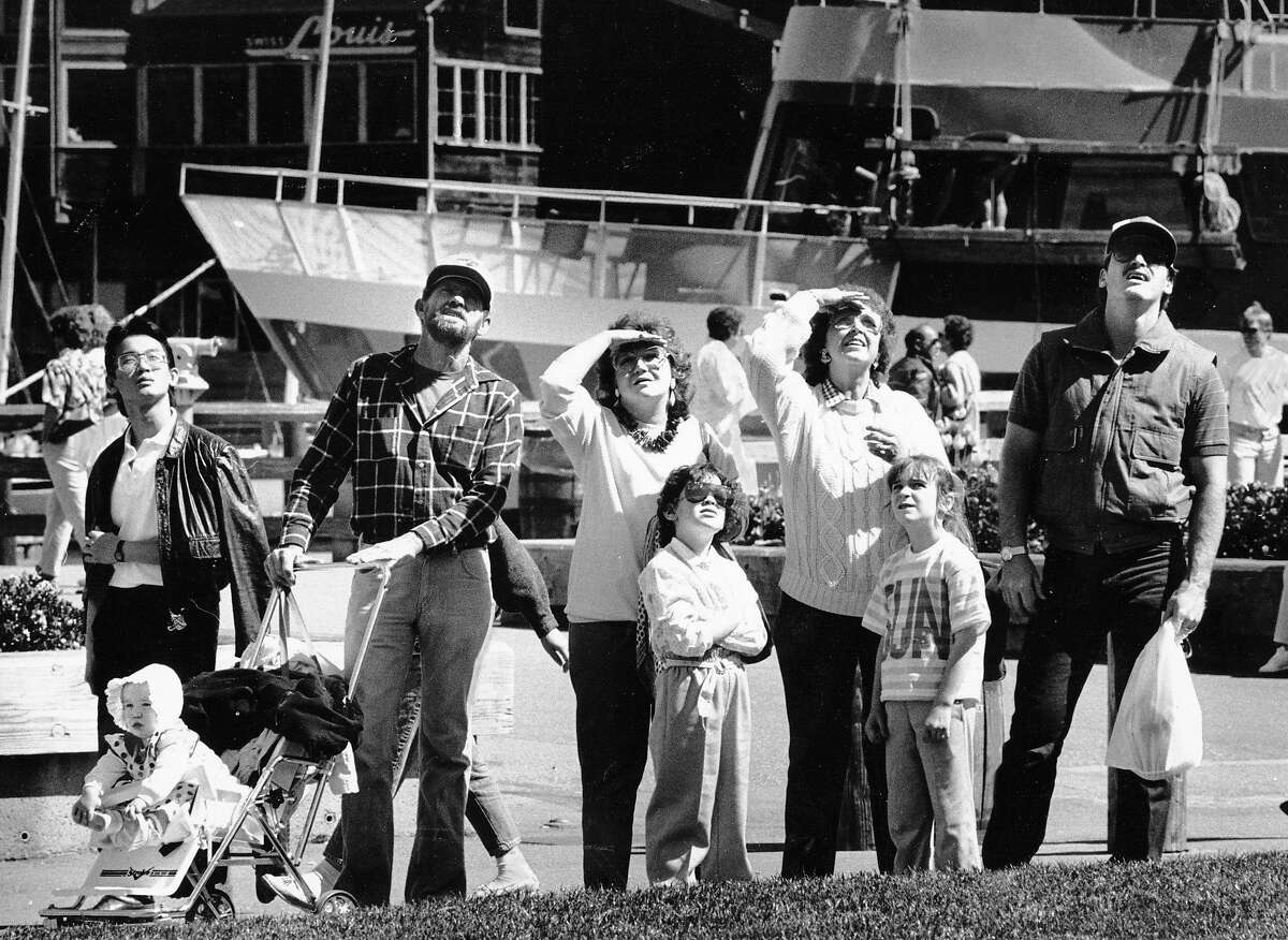 Tourists look skyward to watch a kite-flying contest near Pier 39 on March 29, 1987.