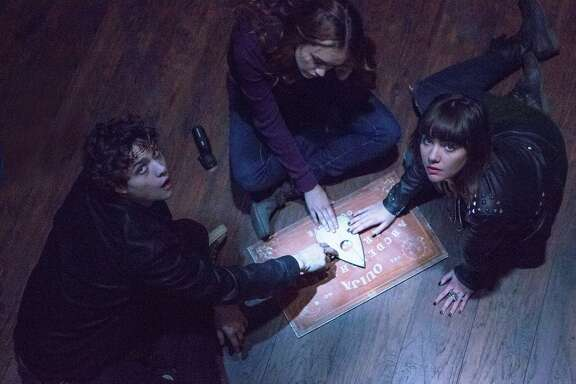 """(L to R) Pete (DOUGLAS SMITH), Laine (OLIVIA COOKE) and Sarah (ANA COTO) play the game in """"Ouija"""", a supernatural thriller about a group of friends who must confront their most terrifying fears when they awaken the dark powers of an ancient spirit board."""
